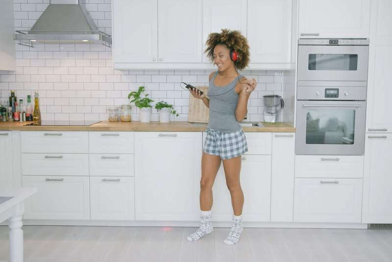 young-woman-dancing-in-kitchen-with-smartphone
