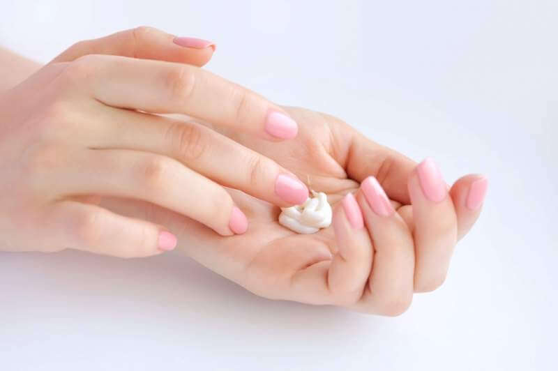 young-woman-with-pink-manicure-applies-cream
