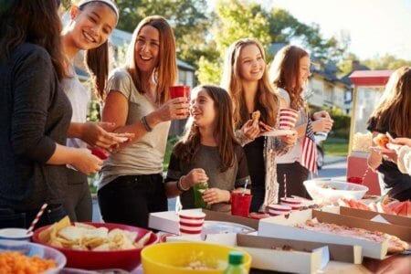 girls-stand-talking-at-a-block-party-food-table