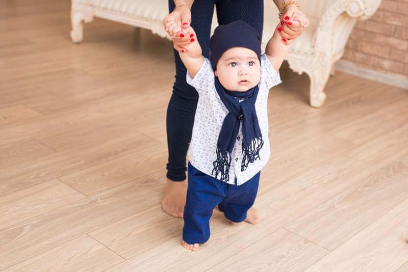 mom-teaching-her-sons-first-baby-steps-indoors