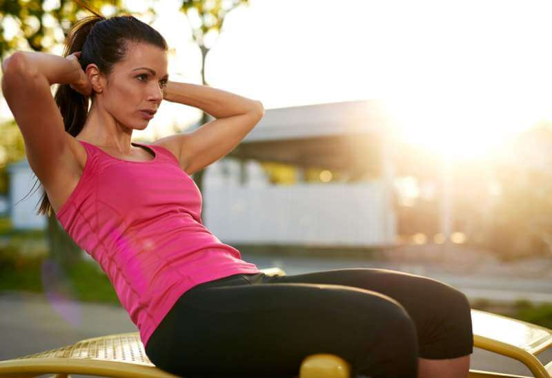 side-view-of-woman-doing-situps-outside