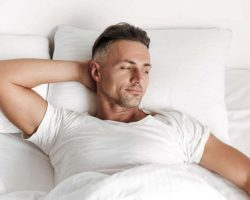 smiling-man-relaxing-in-bed