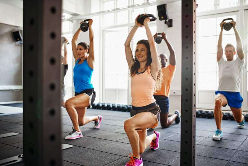 smiling-young-woman-working-out-with-friends