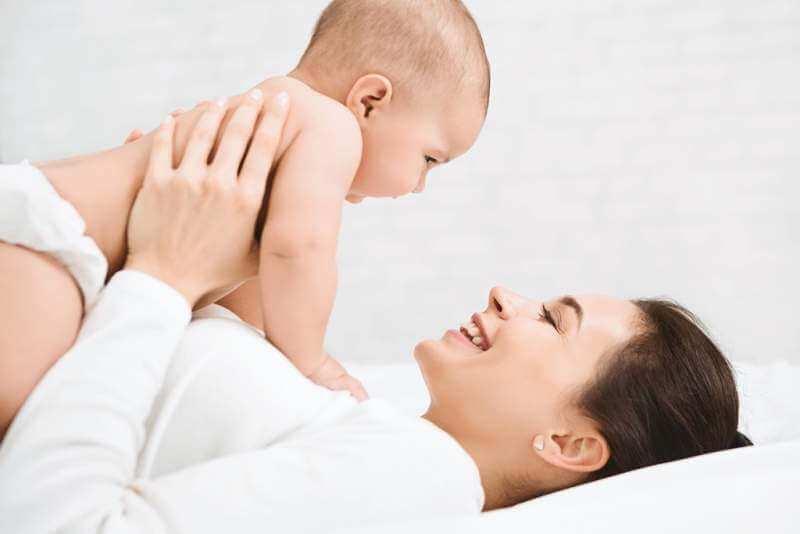 young-mom-holding-her-happy-baby-in-air