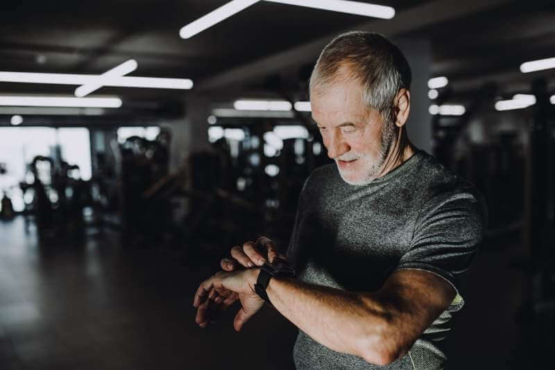 a-cheerful-senior-man-in-gym-measuring-time-while