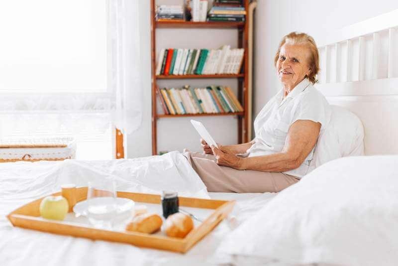 elderly-woman-having-breakfast-in-bed-whilst