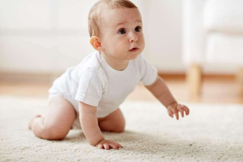 little-baby-in-diaper-crawling-on-floor-at-home