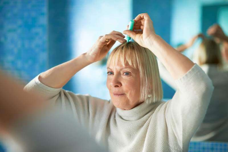 senior-woman-checking-hairline-for-hair-loss