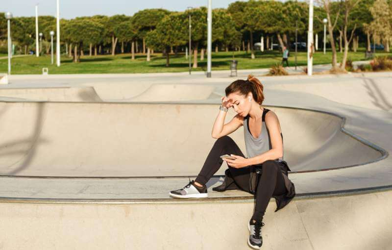 tired-sports-lady-sitting-outdoors-in-park-using