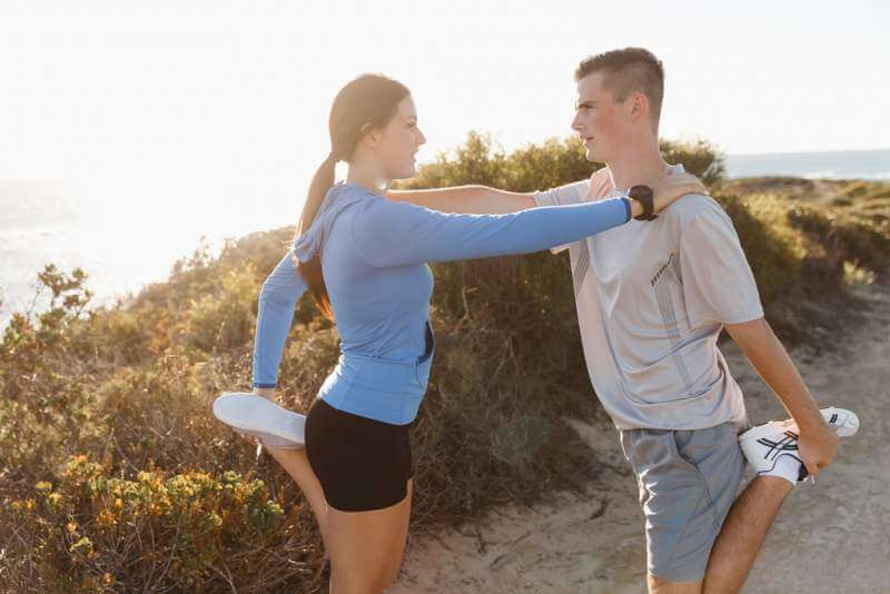 young-couple-on-beach-training-together