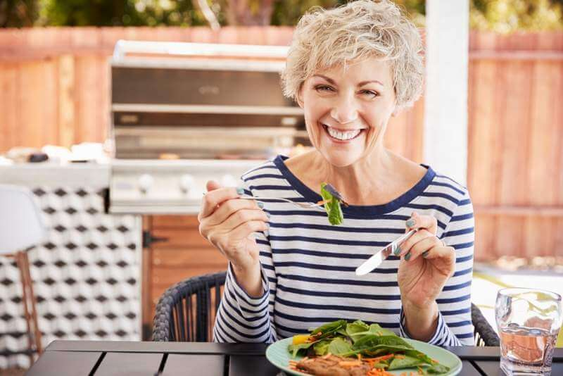 senior-white-woman-eating-lunch-at-a-table-in-her