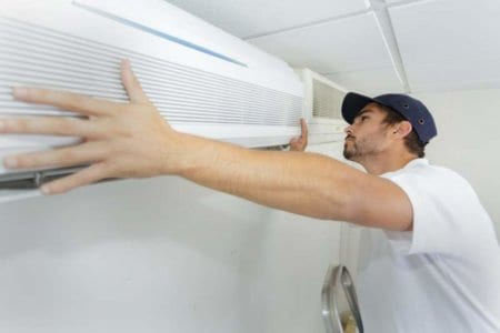 tech-guy-carefully-installing-new-ac