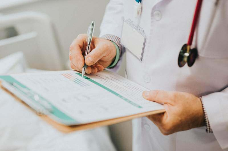 clinician-writing-medical-report