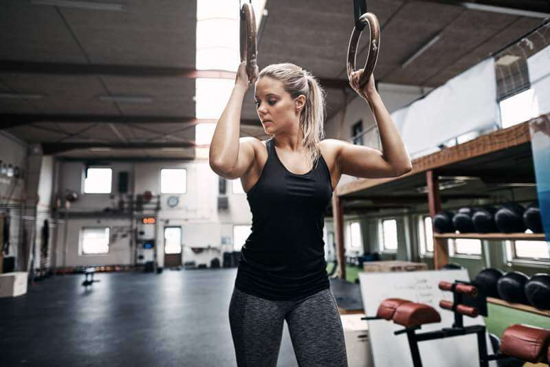 fit-young-woman-exercising-on-rings-in-a-health