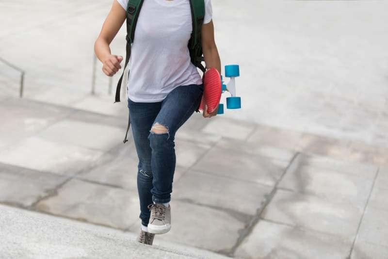 skateboarder-walking-with-skateboard-on-city