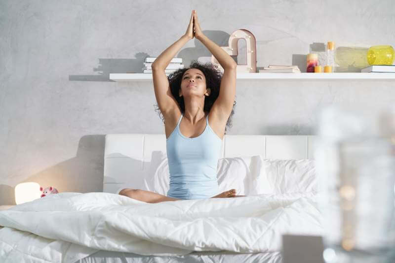 young-african-american-woman-doing-yoga-in-bed