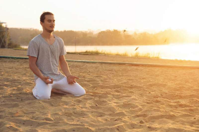 young-attractive-man-meditating-on-the-beach