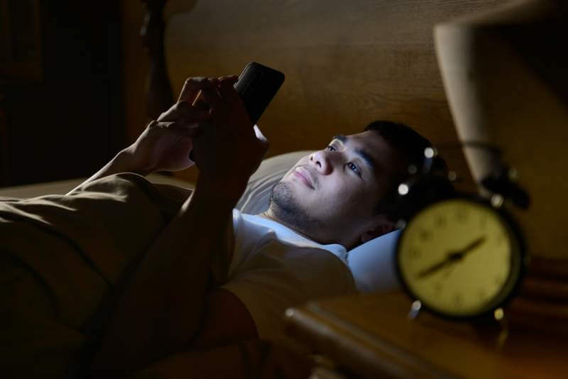 young-man-using-a-smartphone-in-his-bed-at-night