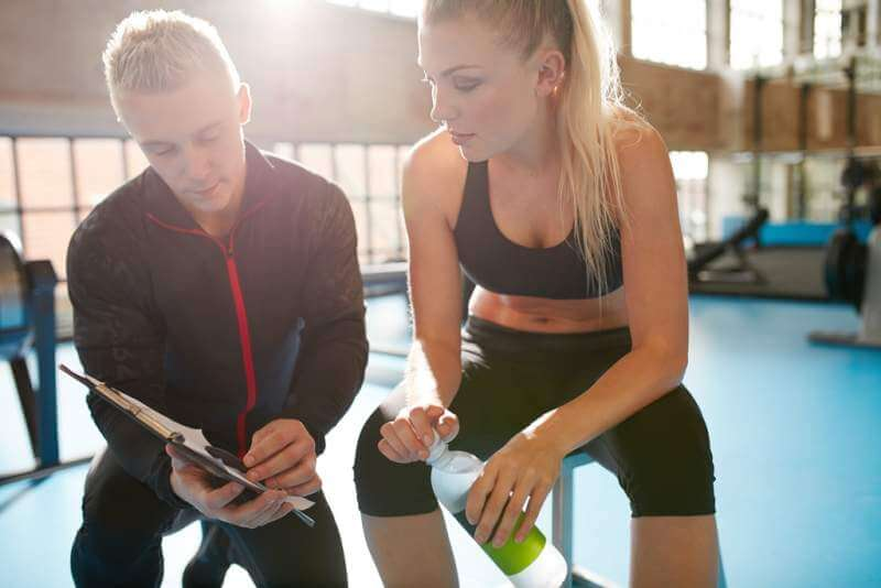 young-woman-with-her-physical-trainer-looking