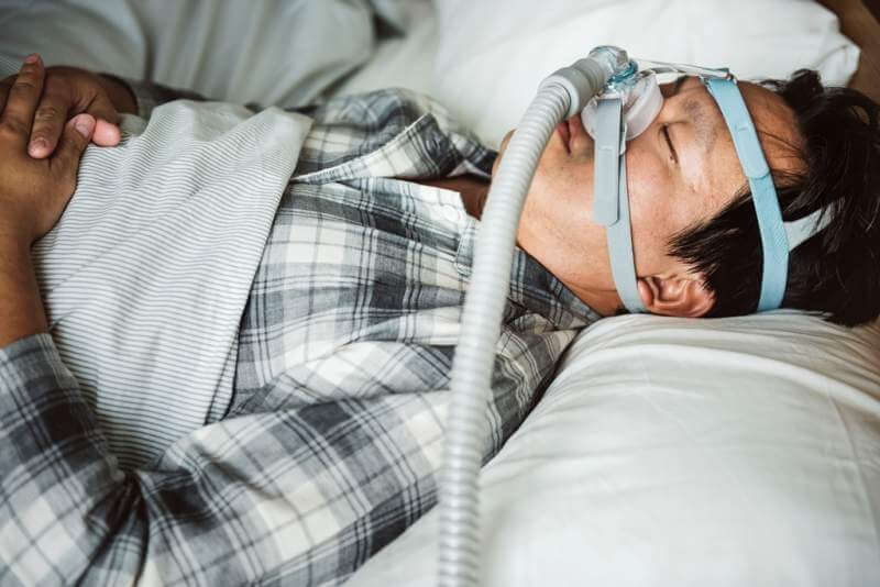 a-man-sleeping-with-anti-snoring-chin-strap