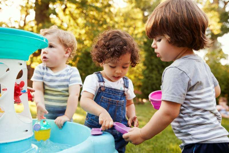 group-of-young-children-playing-with-water-table