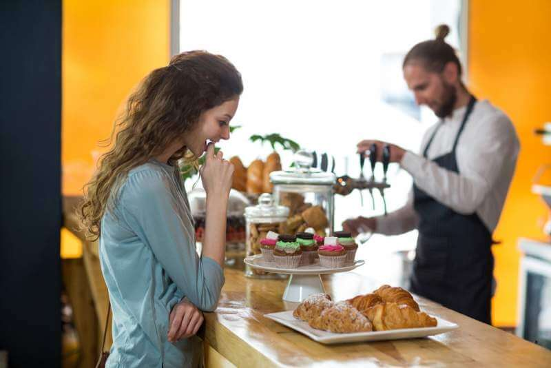 smiling-woman-looking-at-croissant
