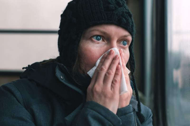 woman-blowing-her-nose-into-paper-handkerchief