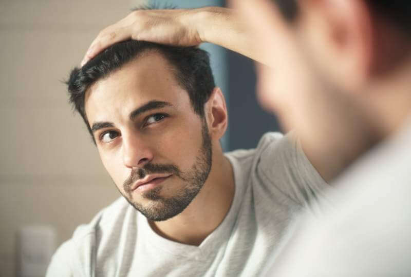 man-worried-for-alopecia-checking-hair-for-loss