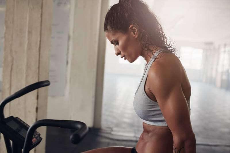 muscular-woman-exercising-on-gym-bike