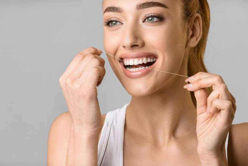 tooth-care-young-woman-using-dental-floss