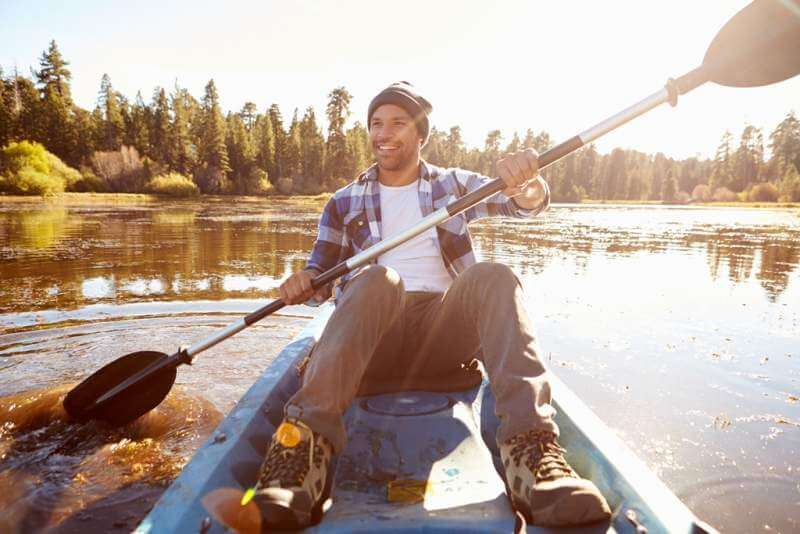 young-man-rowing-kayak-on-lake