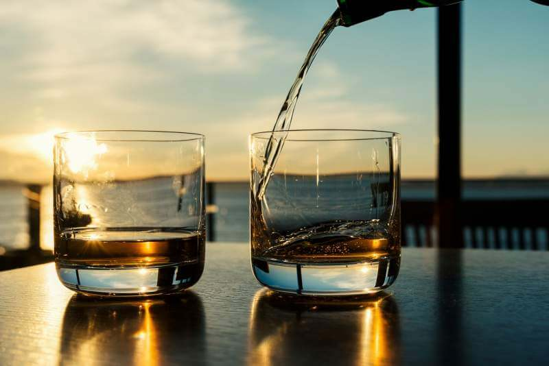 pouring-whiskey-at-sunset