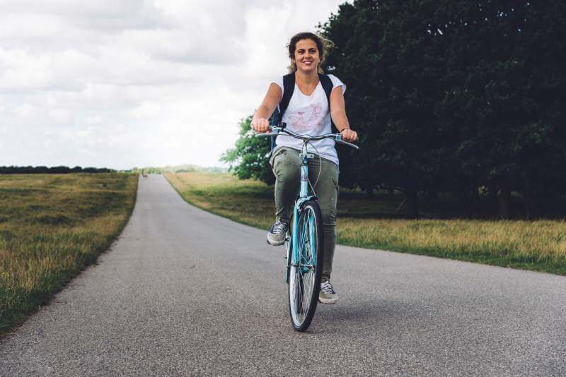 smiling-young-woman-riding-mountain-bike