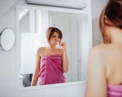 young-women-brushing-her-teeth-in-bathroom
