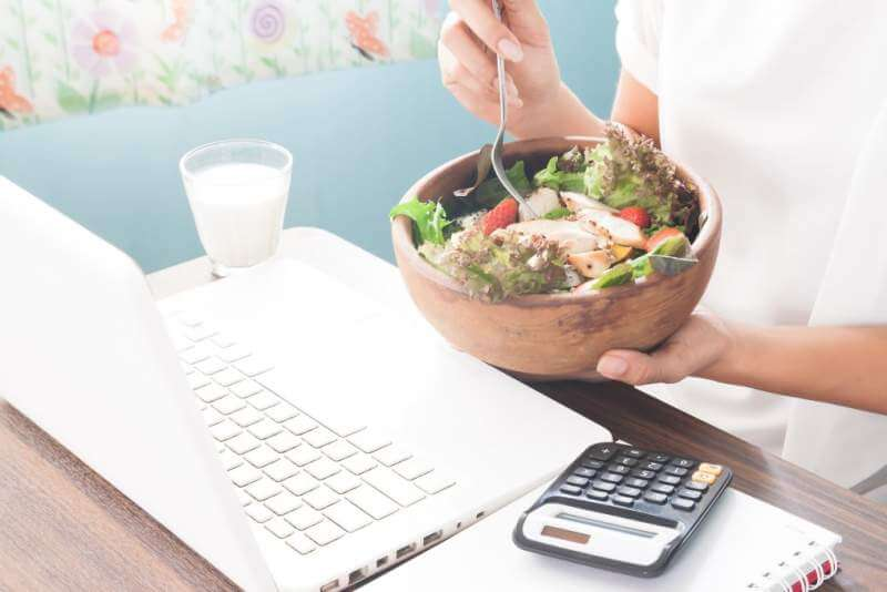 Woman eating chicken salad during working